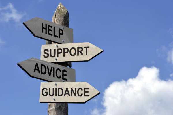 "A wooden post with four arrows that read ""Help,"" ""Support,"" ""Advice,"" and ""Guidance."""